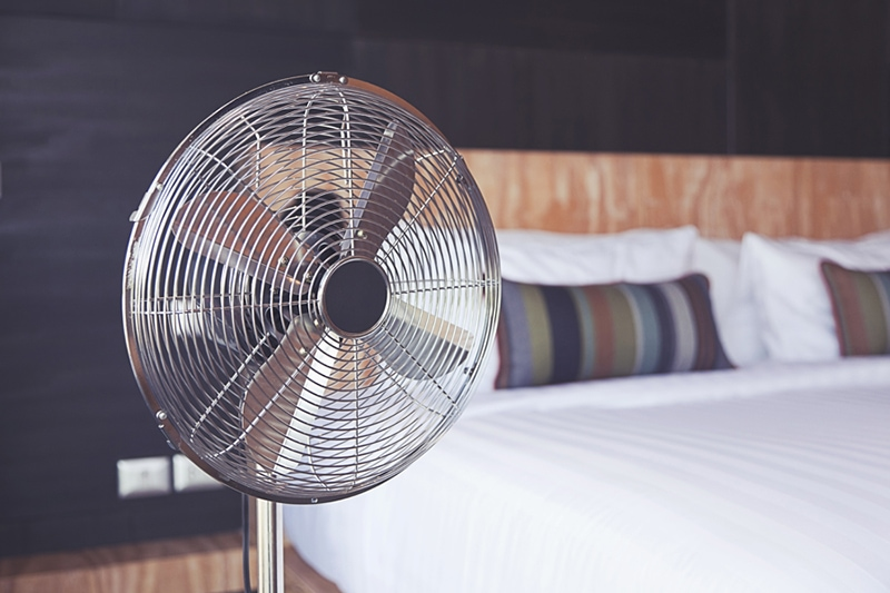 Improve Your Home's Indoor Air Quality, Old electric fan near the bed in the room