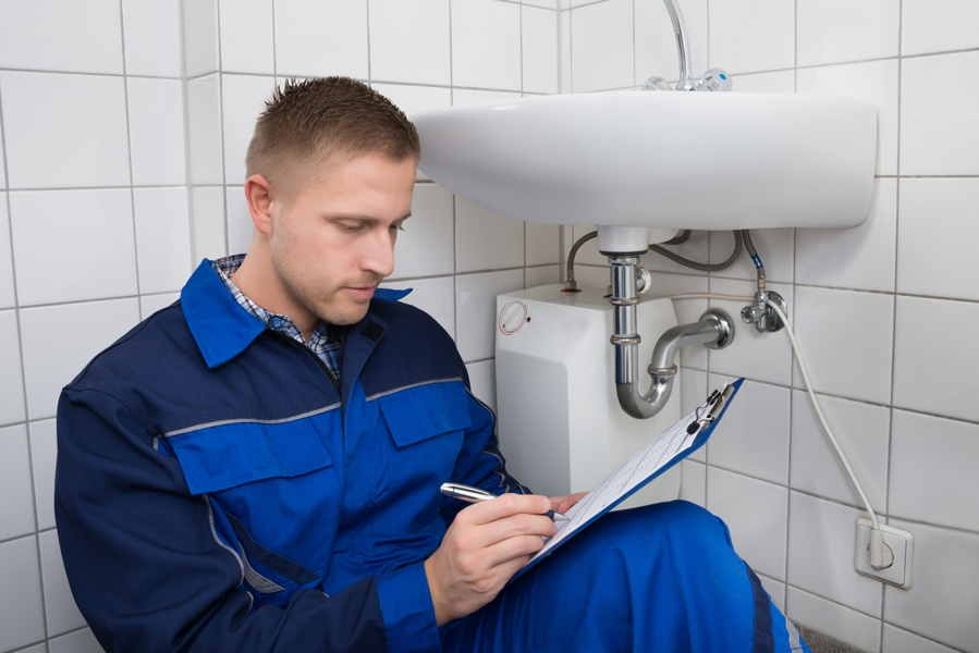 Young Plumber Writing On Clipboard With Pen In Bathroom. What Is a Plumbing Inspection?